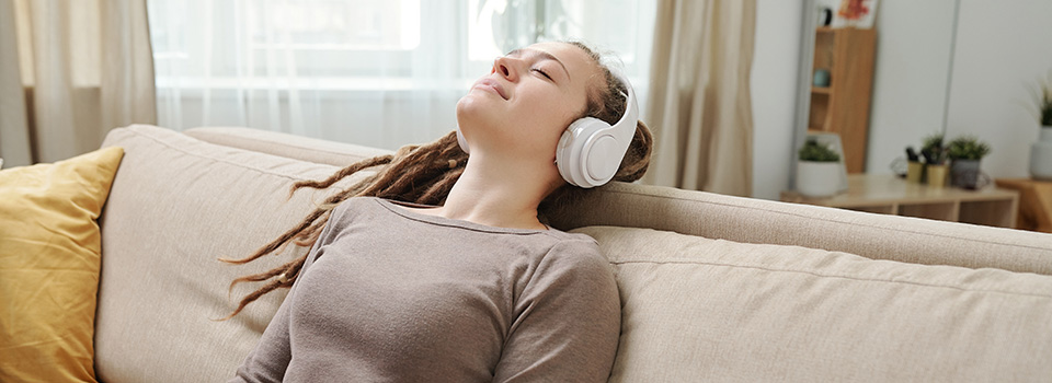anxiety free woman with headphones on sofa after taking hemp derived cbd gummies for anxiety relief.
