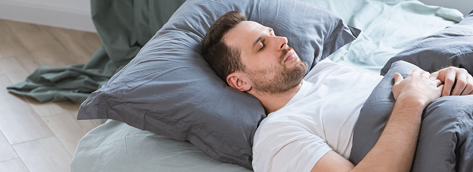 man sleeping well after using cbd tincture oil for sleep aid insomnia