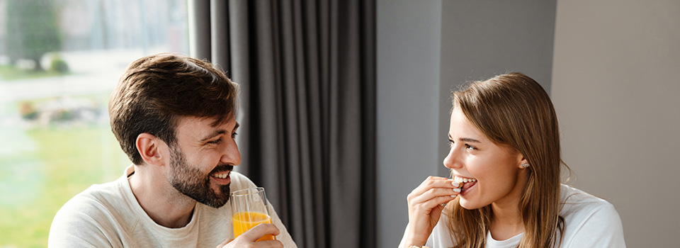 adult couple smiling and eating cbd gummies. Can cbd gummies help with anxiety?